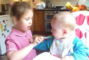 Big sister helping to feed her brother